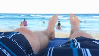 Legs of man laying on beach chair at ocean