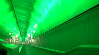 Light tunnel at Detroit Michigan Airport with traveler on escalator 4k