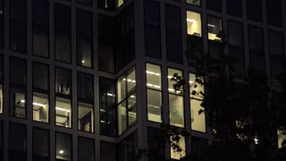 Lights on in office building windows at night 4k