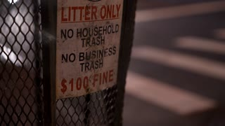 Litter only sign posted on trash bin in city at night 4k