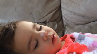 Little girl sleeping on couch with stuffed animal