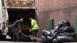 Loading garbage truck with black trash bags in NYC 4k