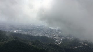 Looking down at Rio de Janeiro from mountain top with foggy clouds