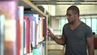 Male browsing books at library