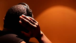 Male DJ listening to Headphones at Club Scene