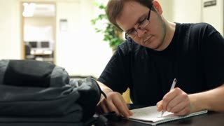 Male student taking notes in notebook