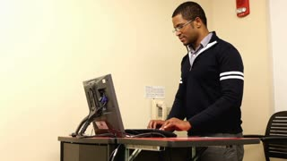 Male using Computer standing up