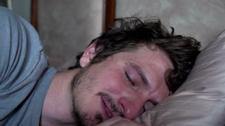 Man crying laying on pillow in bed