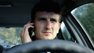 Man driving car talking on cell phone