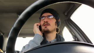 Man driving car while talking on cell phone 4k