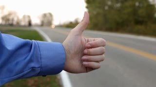 Man holding up thumb on side of road