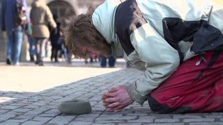 Man kneeling down on city street asking for help