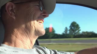 Man laughing and talking while driving car 4k