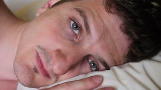 Man laying in bed yawns