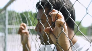 Man locked up grabbing on to fence 4k