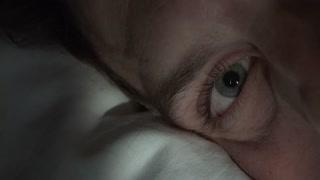 Man looking at camera with eyeball laying on pillow 4k