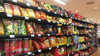 Man looking at chips in grocery store 4k