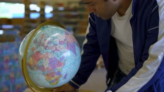 Man looking at world globe in library 4k