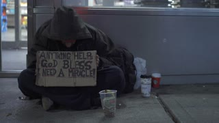 Man on sidewalk with anything helps sign in New York City 4k