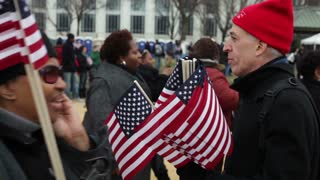 Man passing out flags at inauguration 2013
