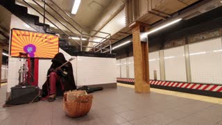 Man performing in subway station as train arrives