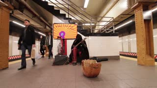 Man playing electric guitar in subway station