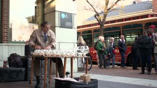 Man playing glass cups as instrument wide angle