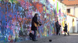 Man playing guitar in front of Lennon Wall