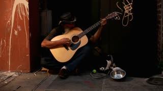 Man playing guitar on street during Mardi Gras 2012