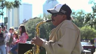 Man playing saxophone for Mardi Gras crowds