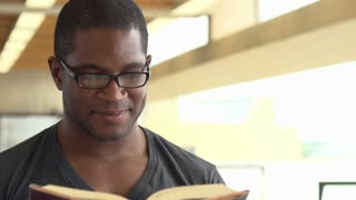Man reading book smiles and laughs