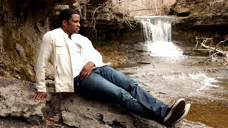Man relaxing on rock near Waterfall