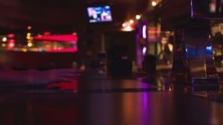 Man sitting at bar watching tv.