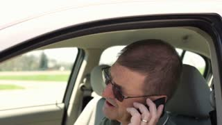 Man sitting in car on cell phone jib shot