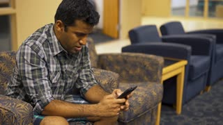 Man sitting in waiting area lounge texting on cell phone 4k