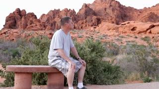 Man Sitting on bench in mountain smiling