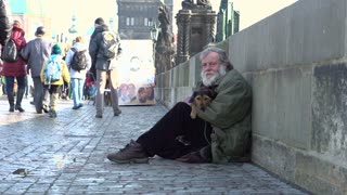 Man sitting on bridge with dog in Prague
