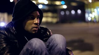 Man sitting on side of City intersection at Night