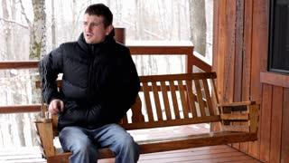 Man sitting on swinging bench puts on hood