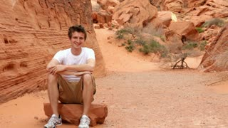 Man Smiling while sitting on Rock in Mountain