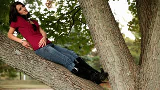 Man sneaking up on Girl sitting on tree branch