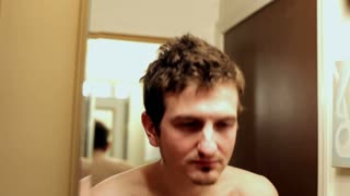 Man splashing water on his face in bathroom
