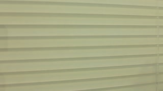 Man Staring through Blinds