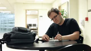Man studying at table with school notes