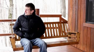 Man swinging on porch in winter jacket