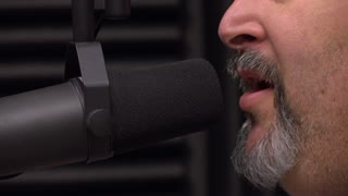 Man talking into recording studio microphone for radio interview 4k