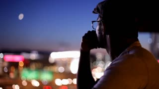 Man thinking with City and moon in background