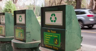 Man throwing away can into recycling in woods 4k.