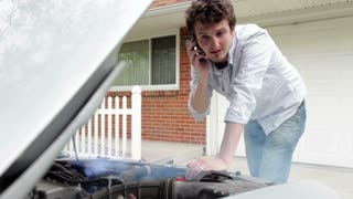 Man trying to fix smoking car in front of house