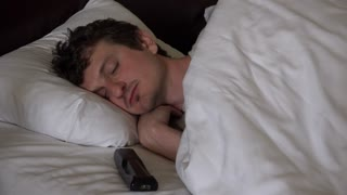 Man wakes up and turn on tv in hotel bed 4k